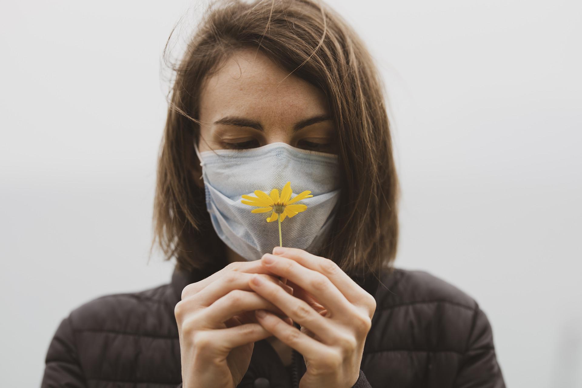 Med munnbind og blomst